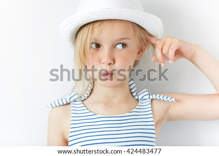 Headshot of angry and irritated preschool girl in white hat and striped dress, gesturing with index finger against her temple: are you crazy? Isolated portrait of little Caucasian 5-year old child - stock photo