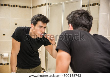 Headshot of attractive young man brushing teeth with toothbrush, looking at himself in mirror - stock photo