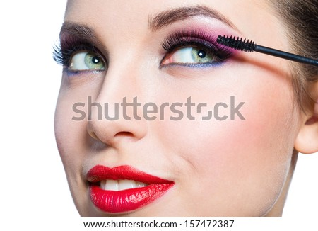 Headshot of female with bright makeup applying mascara on eyelashes, isolated - stock photo
