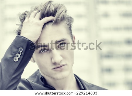 Headshot of handsome blond young man outdoor in city setting, touching hair with his hand, looking away - stock photo