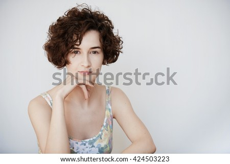 Headshot of pretty Caucasian female model with short brown curly hair, resting chin on her hand, posing in tank floral top against white studio wall with copy space for your advertising content.  - stock photo