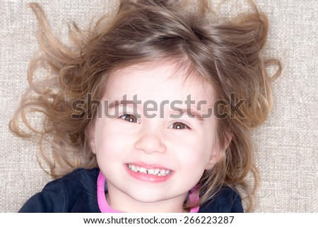 Headshot of young three year old girl lying on a carpet with tousled hair grinning up at the camera with a happy expression - stock photo