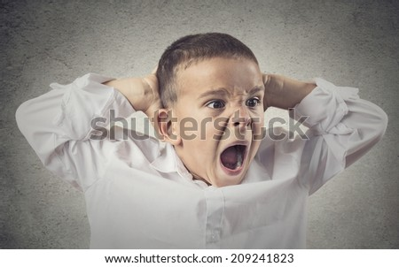 Headshot, Portrait Angry Child Screaming, hands on head isolated grey wall background. Negative Human face Expressions, Emotions, Reaction, life Perception. Conflict, confrontation concept. Behavior - stock photo