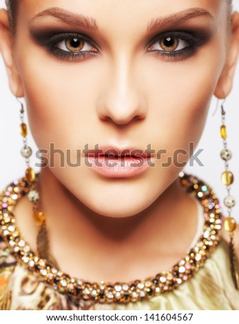 headshot portrait of beautiful young brunette woman in ear-rings and collar on gray - stock photo