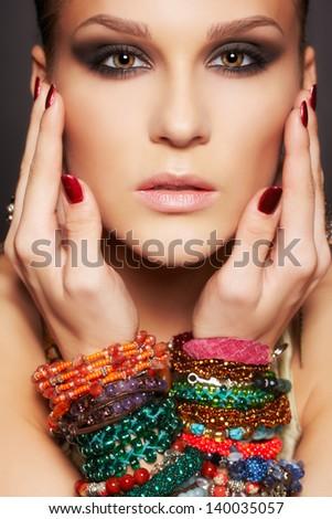 headshot portrait of beautiful young brunette woman posing in multiple bracelets on dark gray - stock photo