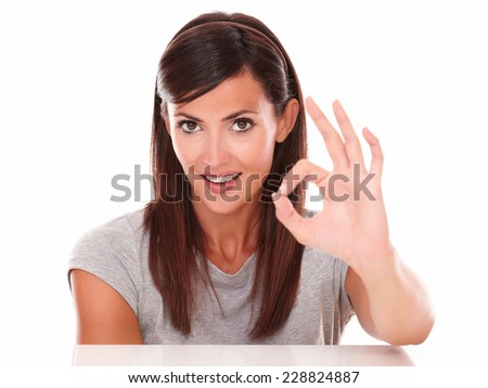 Headshot portrait of cute female with ok sign looking at camera on isolated studio - stock photo