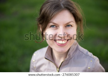 Headshot portrait of happy smiling woman in park - stock photo
