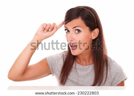 Headshot portrait of surprised woman pointing to her head while looking at camera on isolated white background - stock photo