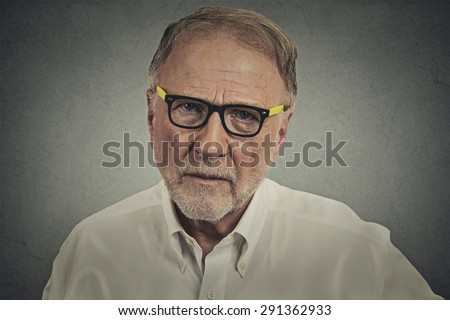 Headshot portrait senior elderly skeptical man with eyeglasses isolated on gray wall background. Human face expressions, emotions, feelings, perception  - stock photo