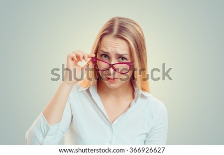 Headshot serious angry bitchy woman wife holding sunglasses down skeptically looking at you isolated green yellow wall background, white shirt. Human face expression body language, attitude perception - stock photo