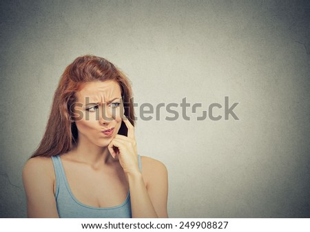Headshot thoughtful skeptical suspicious young woman on grey background  - stock photo