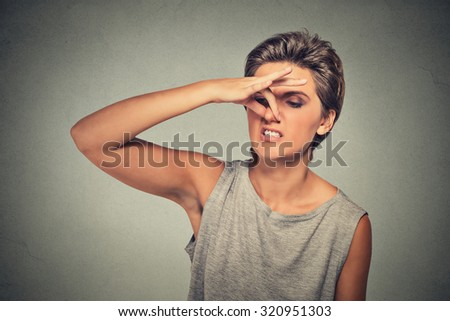 headshot woman pinches nose with fingers hand looks with disgust away something stinks bad smell situation isolated on gray wall background. Human face expression body language reaction - stock photo