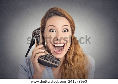 Headshot young happy woman looking excited, holding an high heeled shoe in her hand as a phone isolated on grey wall background. human face expression emotion feelings - stock photo