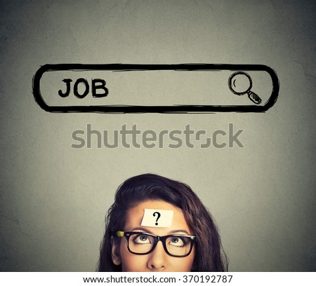Headshot young woman in glasses thinking looking for a new job isolated on gray wall background  - stock photo
