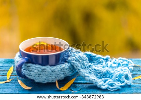 Healing cup of tea in a scarf on blue wooden background - stock photo
