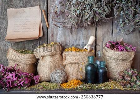 Healing herbs in hessian bags near wooden wall, herbal medicine. - stock photo