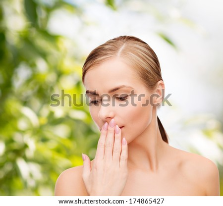 health and beauty concept - clean face of beautiful young woman covering her mouth with hand - stock photo