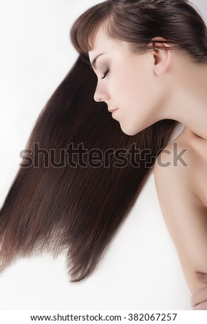 Health and Beauty Concept. Cute Caucasian Brunette Female With Natural Long Hair Posing Against White. Vertical Image - stock photo