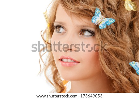 health and beauty concept - happy teenage girl with butterflies in hair - stock photo