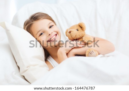 health and beauty concept - little girl with teddy bear sleeping at home - stock photo