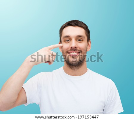 health and beauty concept - smiling young handsome man pointing to eyes - stock photo