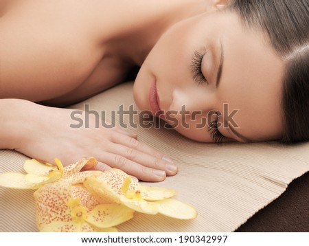 health and beauty, resort and relaxation concept - asian woman in spa salon lying on the massage desk - stock photo