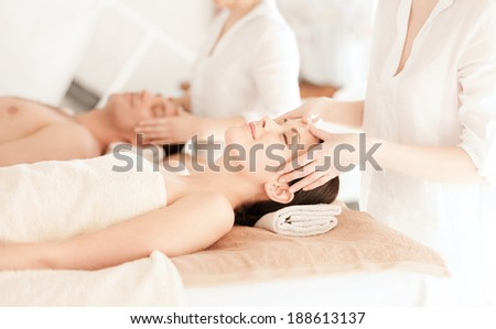 health and beauty, resort and relaxation concept - couple in spa salon getting facial massage - stock photo
