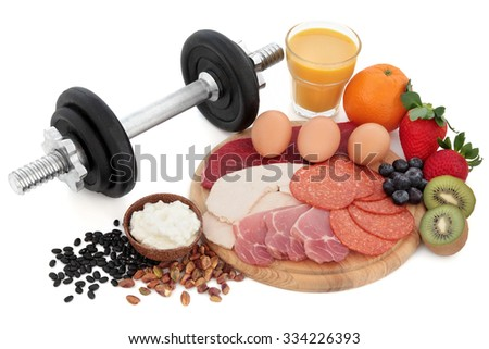 Health and body building high protein food of meat, nuts, pulses, cottage cheese, fruit and smoothie juice with dumbbell weights over white background. - stock photo