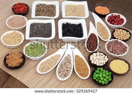 Health and body building super food with whey protein, wheat grass, acai berry and maca powder, nuts, seeds, pulses, grains, cereals, fruit, vegetables and peanut butter. - stock photo