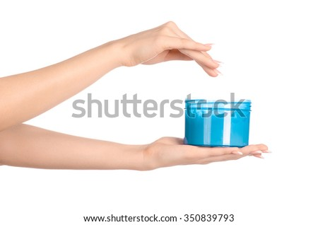 Health and body care topic: a woman's hand holding a blue jar with cream isolated on white background - stock photo