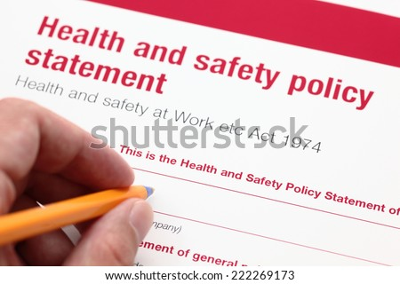 Health and safety policy statement and hand with ballpoint pen. - stock photo