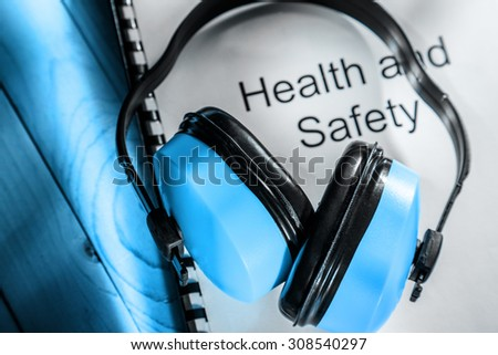 Health and safety register with earphones in blue toning - stock photo