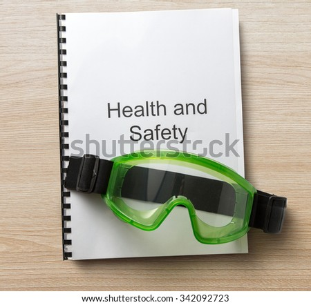 Health and safety register with goggles in closeup - stock photo