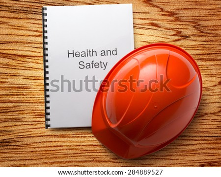 Health and safety register with helmet in closeup - stock photo