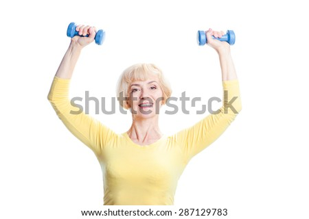 Health and sport. Cheerful aged woman exercising with dumbbells looking at camera. Isolated on white. - stock photo