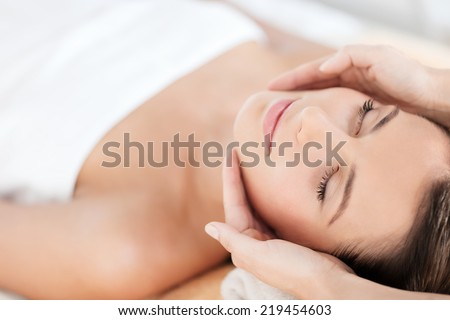 health, beauty, resort and relaxation concept - beautiful woman in spa salon getting face treatment - stock photo