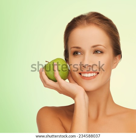 health, beauty, vegetarian food and people concept - smiling young woman with apple over green background - stock photo