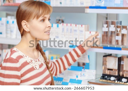 Health care consultancy. Young attractive woman addresses someone in a drugstore in terms of beauty care products - stock photo