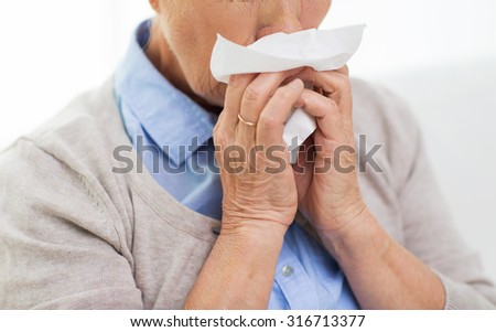 health care, flu, hygiene, age and people concept - close up of sick senior woman blowing nose to paper napkin at home - stock photo