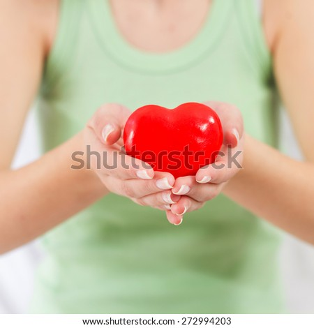 Health Care Love Support Red Heart in female hands. - stock photo