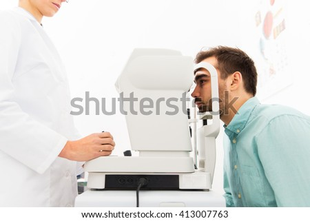 health care, medicine, people, eyesight and technology concept - close up of optometrist with autorefractor checking patient vision at eye clinic or optics store - stock photo