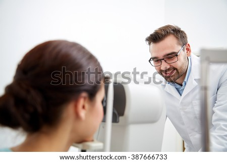 health care, medicine, people, eyesight and technology concept - optometrist with non contact tonometer checking patient intraocular pressure at eye clinic or optics store - stock photo