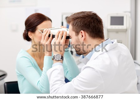 health care, medicine, people, eyesight and technology concept - optometrist with pupilometer checking patient intraocular pressure at eye clinic or optics store - stock photo