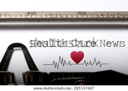 Health care news printed on an old typewriter with heart beat pulse sketch - stock photo