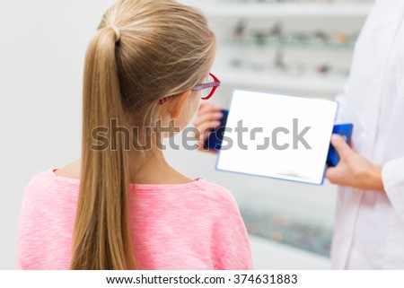 health care, people, eyesight and vision concept - close up of optician with mirror helping little girl to choose glasses at optics store - stock photo