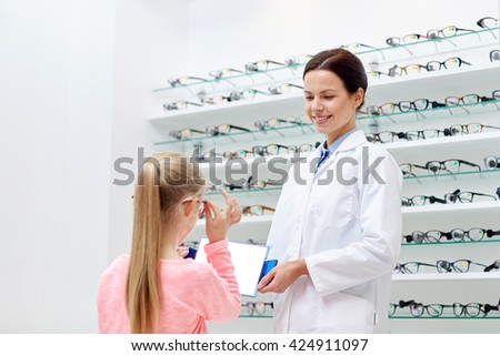 health care, people, eyesight and vision concept - optician with mirror helping little girl to choose glasses at optics store - stock photo
