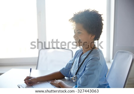 health care, profession, people and medicine concept - happy female doctor or nurse with clipboard and pen writing at hospital - stock photo