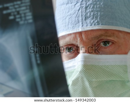 Health care professional  intensely studies x-ray results prior to surgery. Selective focus on eyes.  Would make good hospital, physician, doctor, surgeon illustration. Photographer as model.  - stock photo