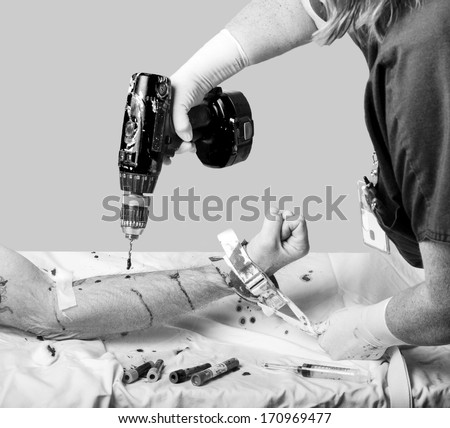 Health care worker holding a patients arm with a restraint using a drill for drawing blood - stock photo
