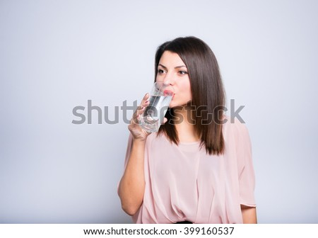 Health Concept: closeup of a young beautiful woman is drinking a glass of water - stock photo